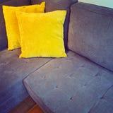 Corner sofa with bright yellow cushions Stock Photo
