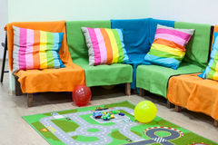 Corner sofa with colorful striped pillows, balloons on floor in the room Royalty Free Stock Images