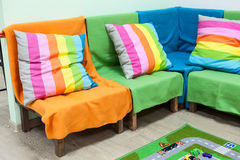 Corner sofa with colorful striped pillows in room Stock Photography