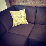 Corner sofa with cushion near brick wall Stock Photography