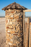 Corner stone tower with a wooden conical roof on the beach. Royalty Free Stock Photo