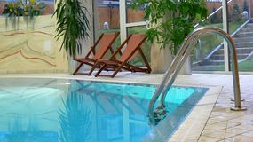Corner of swimming pool. A partial view of a swimming pool and patio with two lounge chairs at a luxury hotel Stock Photo