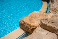 Corner of a swimming pool with decorative stones Royalty Free Stock Photography