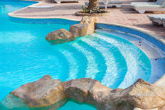 Corner of a swimming pool with decorative stones Stock Photo