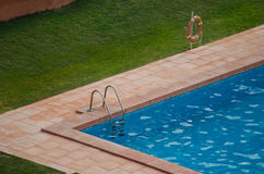 Corner of a swimming pool, outdoors. Corner of swimming pool outside with grass around it Royalty Free Stock Photos