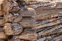 Corner of the wall of a very old log house, wooden background. stock photography