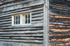 Corner of Weathered Barn Wall with Windows and Rustic Wood Siding. Stock Photo