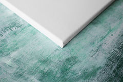 Corner of the white primed canvas. On the stretcher. Green vintage wooden board on background Stock Image