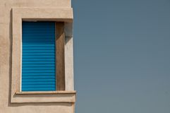 Corner window with blue shutters Royalty Free Stock Image