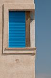 Corner window with blue shutters Royalty Free Stock Images