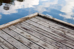 Corner of a wooden dock. Corner of a dock with a boat cleat and clouds reflected in the water Stock Images