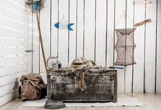 Corner of wooden room with things for fishing and big old chest Stock Image