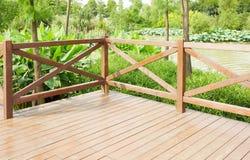 Wooden deck wood patio outdoor garden terrace balcony. Corner of empty wood deck, wooden patio, balcony  terrace with balustrade by riverside in garden Royalty Free Stock Photo