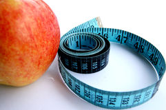 Cornered in a diet. This is an image of a red apple and a blue measuring tape. (Apple uniquely cornered to emphasis- how personal dieting can be. The drop of stock photo
