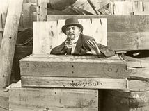 Cornered man behind wooden crates pointing gun Stock Photo