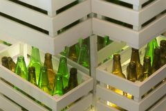 Corners of shelves made from white painted wood crates with transparent glass bottles inside. Retro style beer bottle rows. stock image
