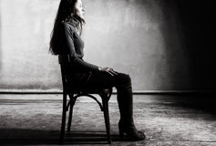 Corners. Young girl sitting on a chair in the gloomy place Stock Photography