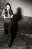 Corners. Young girl sitting on a chair in the gloomy place Stock Photos
