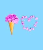 Cornet de crème glacée avec des fleurs et la forme de coeur des pétales au-dessus du fond bleu Image libre de droits