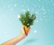 Cornet de crème glacée d'arbre de Noël chez la main de la femme sur le fond bleu de Ligth Concept d'an neuf Composition minimale  photographie stock libre de droits