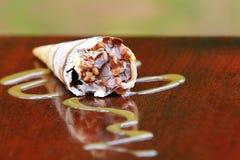 Cornet de crème glacée sur une table souillée par bois photographie stock