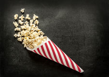 Cornet popcorn on black chalkboard - cinema snack menu. Background layout with free text space Royalty Free Stock Photo