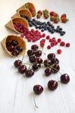 Cornets de crème glacée doux de gaufre avec des framboises, des cerises, des fraises et des myrtilles au-dessus du fond en bois b photos stock