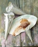 3 cornets de crème glacée emballés en papier argentés un ont épluché de retour sur le cornet de crème glacée de chocolat complété Photographie stock libre de droits