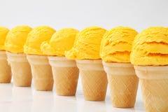 Cornets de crème glacée jaunes dans une rangée Photographie stock libre de droits