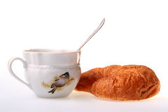 Cornetto and a cup. With tea in a cup a teaspoon Stock Image