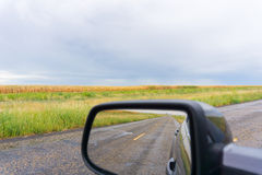 Cornfields of Texas ahead and in rear view mirror. Cornfields of Texas ahead and in rear view mirror moving along the long straight rural roads and golden stock photography