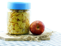 Cornflake in glass contain and red apple. Breakfast with corn flakes in glass container and apple Royalty Free Stock Images