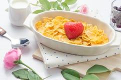 Cornflakens sädesslag och frukt i den vita bunken med maler på träta Royaltyfria Bilder