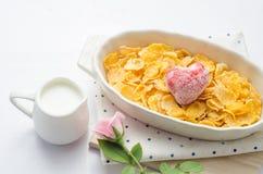 Cornflakens sädesslag och frukt i den vita bunken med mjölkar på träta Fotografering för Bildbyråer