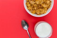 Cornflakes śniadaniowego zboża puchar z mlekiem i łyżką na czerwień plecy Zdjęcia Royalty Free