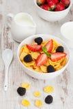 Cornflakes avec des baies dans une cuvette et un lait pour le petit déjeuner, fin Image stock