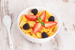 Cornflakes with berries in a bowl and milk for breakfast, close- Stock Photo