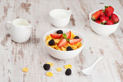 Cornflakes with berries in a bowl and milk for breakfast Stock Photo