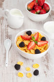 Cornflakes with berries in a bowl and milk for breakfast Royalty Free Stock Images