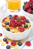 Cornflakes with berries in a bowl, milk and orange juice Stock Images