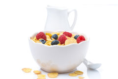 Cornflakes with berries and jug of milk, isolated. Cornflakes with berries and jug of milk, close-up, isolated on white Royalty Free Stock Image