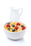 Cornflakes with berries and jug of milk, isolated Stock Image