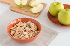 Cornflakes in bowl, fresh apples both whole and cut in pieces on wooden board Royalty Free Stock Images