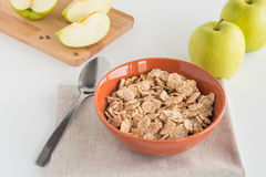 Cornflakes in bowl, fresh apples both whole and cut in pieces on wooden board Stock Photos