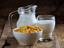Cornflakes in bowl and glass of milk on wooden table Stock Image