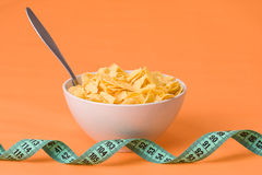 Cornflakes in bowl and measuring tape Royalty Free Stock Image