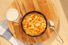 Cornflakes breakfast cereal in the bowl with glass of milk on wood table. Sweet cornflakes breakfast cereal in the bowl with glass of milk on the wooden table Royalty Free Stock Photography