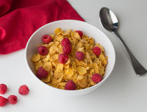Cornflakes breakfast cereal with raspberries in bowl on white ta. Ble with selective focus Royalty Free Stock Photos