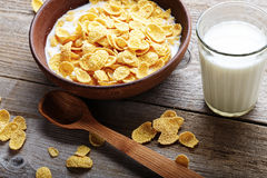Cornflakes in a brown clay plate on a worn wooden background, next is a glass of milk and a spoon Stock Image