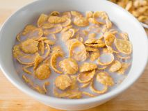 Cornflakes cereal breakfast from the bag to the bowl. Cornflakes cereal breakfast on wooden table royalty free stock image